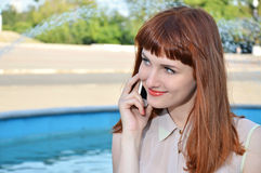 The girl speaks by mobile phone on the stree Royalty Free Stock Image