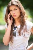 Girl speaks on phone. Long-haired girl speaks on mobile phone stock photo
