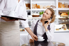 The girl speaks by phone in cafe Stock Photo