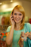 Girl speaks on the phone in a lady's wear shop. The young beautiful woman laughs and talks by a mobile phone in a supermarket in lady's wear section Stock Photo