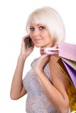 The girl speaks with purchases by phone. In shop Royalty Free Stock Photo