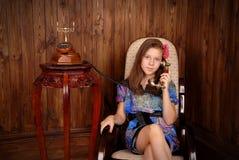 Girl speaks by retro phone Stock Image