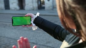 Girl speaks on a smartphone the greenscreen of the phone. Waves the hand to the people that they see on the screen