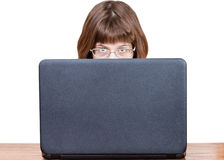 Girl with spectacles looks over cover of laptop Stock Image