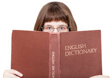 Girl with spectacles looks over English Dictionary Royalty Free Stock Images