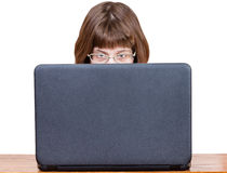 Girl with spectacles reads from laptop screen Royalty Free Stock Photo