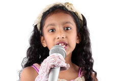 Girl in a Speech. A portrait of a cute little Indian girl making a speech, holding a mic on white studio background Stock Photography