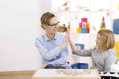 Girl and speech therapist giving each other high five royalty free stock images