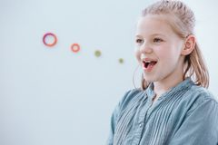 Girl at speech therapy class. Young girl with blonde hair enjoying being at a speech therapy class Stock Photo