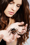 Girl with spider. Close-up portrait of girl holding brachypelma smithi spider in her hands Stock Photo