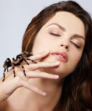 Girl with spider. Close-up portrait of girl with brachypelma smithi spider sitting on her hand Stock Image