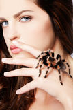 Girl with spider. Close-up portrait of girl with brachypelma smithi spider creeping over her hand Royalty Free Stock Photography