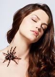 Girl with spider. Close-up portrait of girl with brachypelma smithi spider creeping over her neck Stock Photography