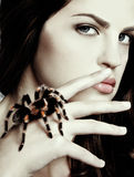 Girl with spider. Close-up portrait of girl with brachypelma smithi spider creeping over her hand Stock Photo