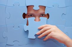 Girl spies through a blue puzzle Stock Image