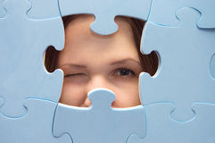 The girl spies through a blue puzzle Royalty Free Stock Photos