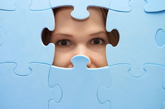 The girl spies through a blue puzzle Stock Photos