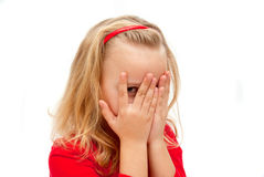 Girl spies. Child covered his face spying Stock Photo