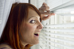 Girl spies through the window Stock Photos