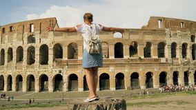 The girl is spinning near the Colosseum in Rome. She`s happy. 4k stock video footage