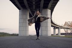 The girl spinning on the road under the bridge over the river stock photo