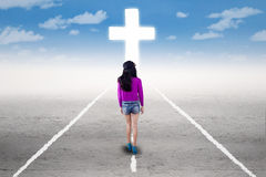 Girl in a spiritual journey with a cross Stock Photo