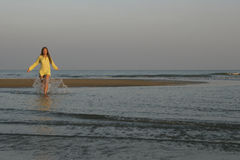 Girl and splashes. Young girl walking in waters of the ocean Stock Photos