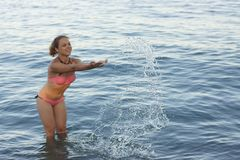 The girl splashes in the sea water. royalty free stock image