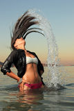 Girl splashing the sea water with her hair Royalty Free Stock Images