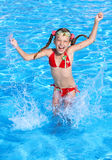 Girl  splashing in swimming pool. Stock Image
