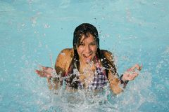 Girl splashing in water. A view of a pretty teenage girl splashing water as she enjoys swimming in a pool Royalty Free Stock Photos
