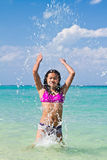 Girl splashing in the water at the beach Royalty Free Stock Photography