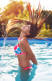 Girl splashing water with hair in pool Royalty Free Stock Images