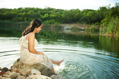 Girl splashing water of lake Stock Images