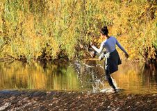 Girl splashing water on weir. Tropical girl - young Papuan woman splashing and kicking water on weir of river Malse with colorful autumn trees behind in Rimov Royalty Free Stock Photos