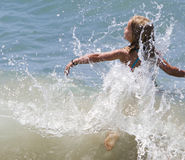 Girl Splashing through Wave. Young girl boldly splashes through ocean wave, water stopped, her foot is visible through water as she floats to top of wave Stock Photo