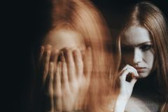 Girl with split personality disorder. Close-up of a blurred face of a young girl with split personality disorder against black background stock images