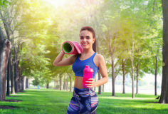Girl with sport bottle and yoga mat in summer park Stock Photography
