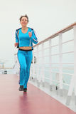 Girl in sport dress running on cruise liner deck Stock Photography
