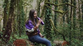 Girl in a sport jacket is sitting on the stump in a forest and unscrew the lid of the thermal bottle to drink from it. A girl in a sport jacket is sitting on stock video