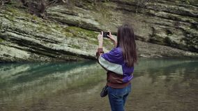 Girl in a sport jacket takes the picture of a beautiful view of the mountain lake on the phone. A girl in a sport jacket takes the picture of a beautiful view stock footage