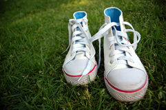 Girl sport shoes in the grass. A pair of white shoes in the grass Stock Photo