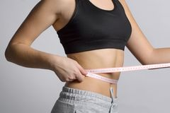 A girl in a sport suit will measure her waist with a flexible ru Stock Image
