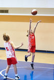 Girl in sport uniform playing basketball Stock Photos