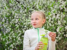 Girl in sports clothes holding a bottle of refreshing drink in cherry blossoms. royalty free stock photography