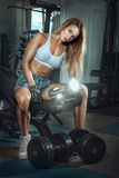 The girl with a sports figure shakes muscles. Stock Image