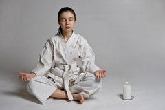 The girl in a sports kimono meditates. The girl in a sports kimono in a relaxation pose Royalty Free Stock Photo