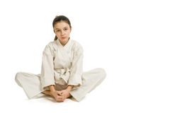 The girl in a sports kimono rest. The girl in a sports kimono has a rest on the white background Stock Photo