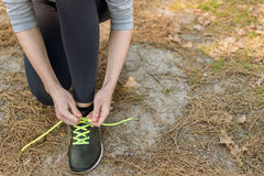 Girl in sports pants and hoodie, sitting tying shoelaces on spor Stock Images