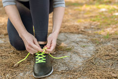 Girl in sports pants and hoodie, sitting tying shoelaces on spor Royalty Free Stock Photography